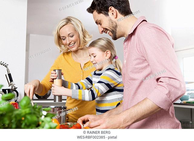 Mother, father and daughter cooking in kitchen