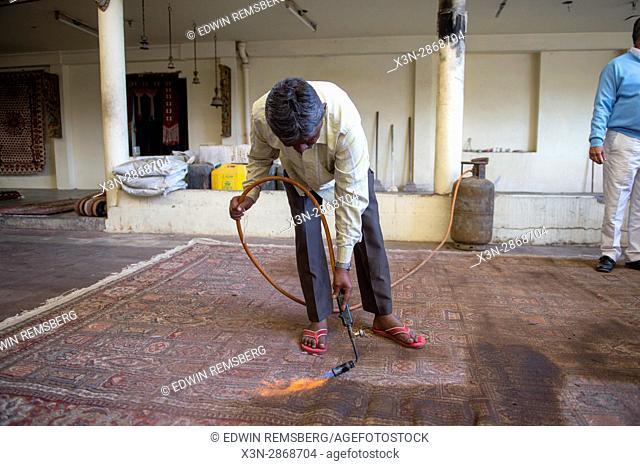 Jaipur, India - Indian man burning oriental rug to rid of extra threads