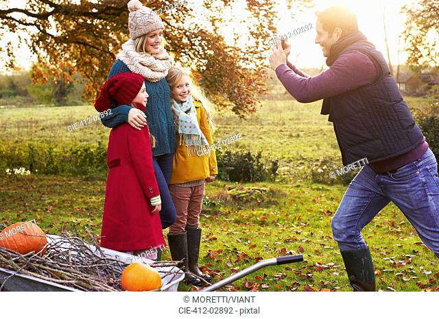 Father taking picture of family outdoors