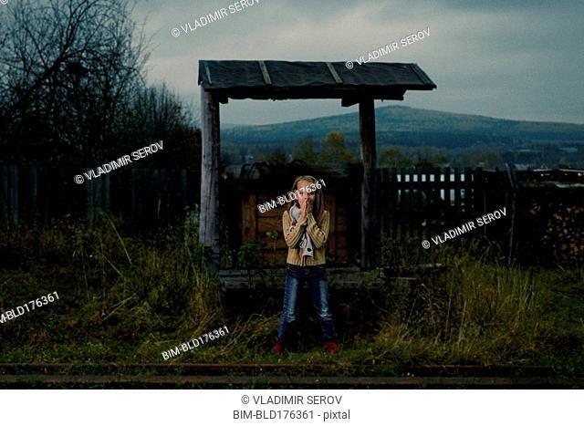 Caucasian girl waiting at rural train stop