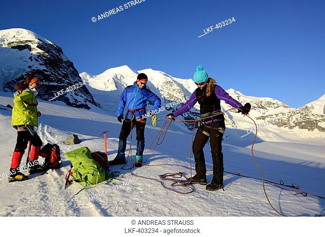 Three mountaineers preparing a roping party, Cambrena glacier, ascent to Piz Palue, Grisons, Switzerland