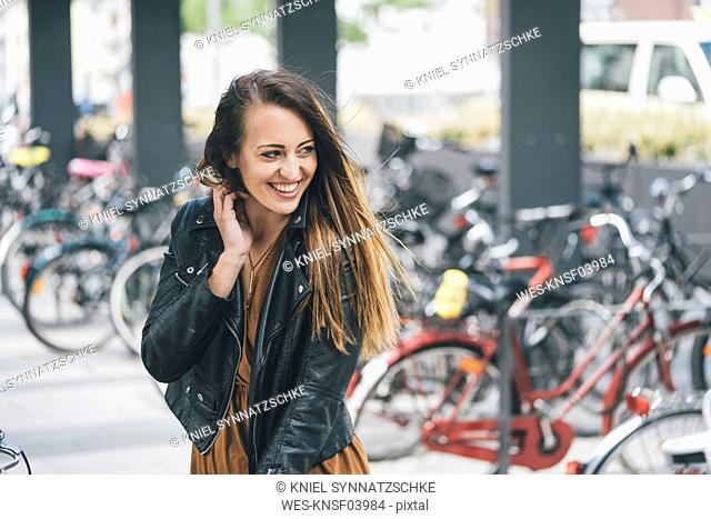 Portrait of happy young woman at bicycle parking station in the city