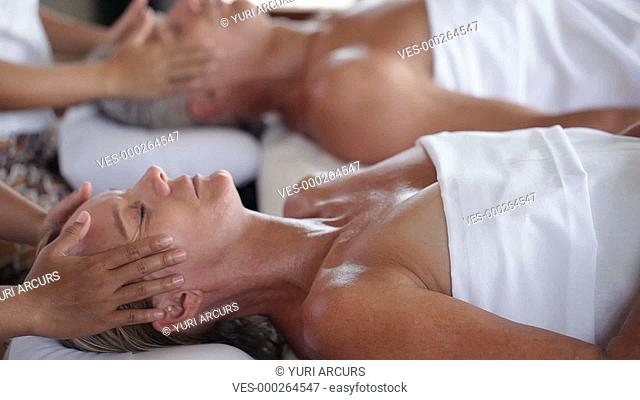 A mature couple receiving relaxing facial massages at the same time