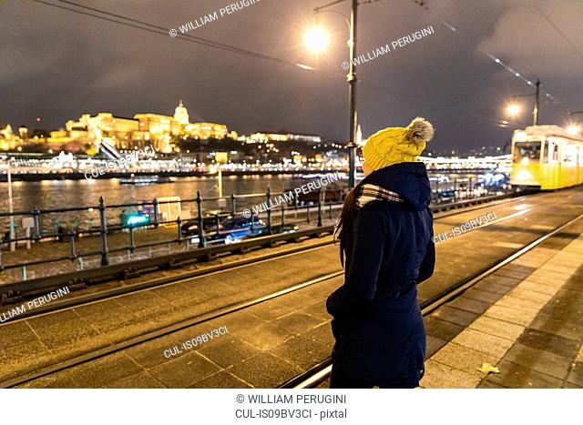 Woman enjoying scenery by river at night, Budapest, Hungary