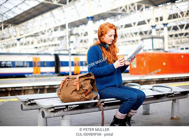 Woman on bench on train station platform, London