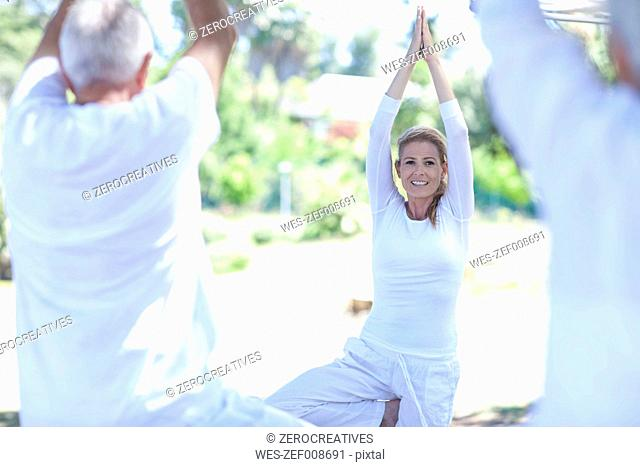 Elderly couple practicing yoga together with instructor