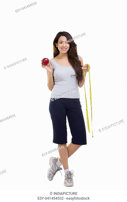 Portrait of woman holding apple and measuring tape
