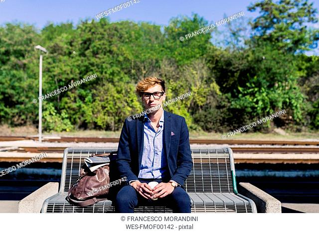 Young businessman with coffee to go sitting on bench at platform
