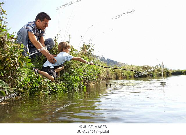 Father and son reaching for boat