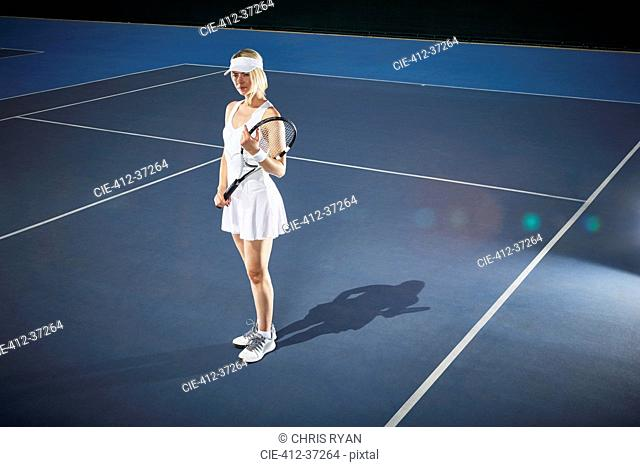 Young female tennis player holding tennis racket on sunny blue tennis court