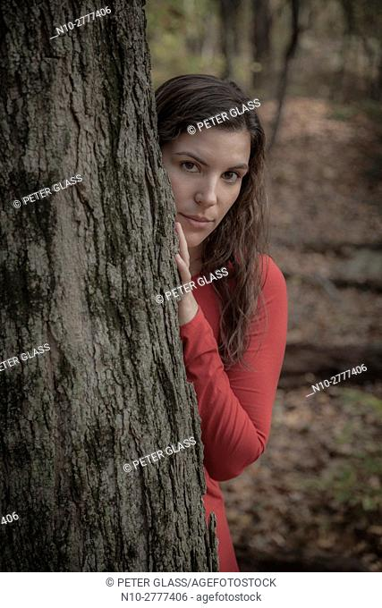 Young woman in a red dress standing behind a tree in the woods during autumn