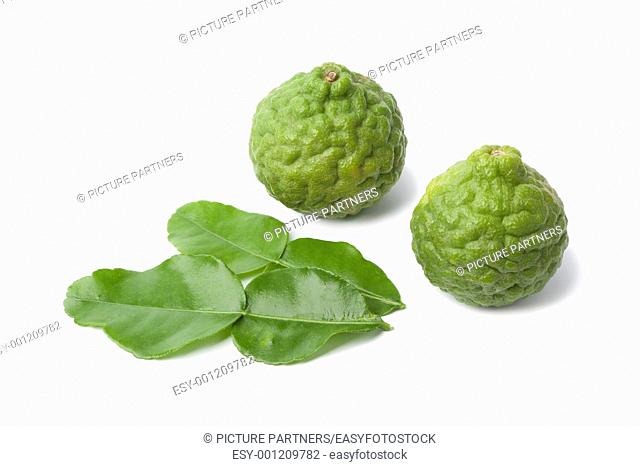Kaffir limes and leaves on white background