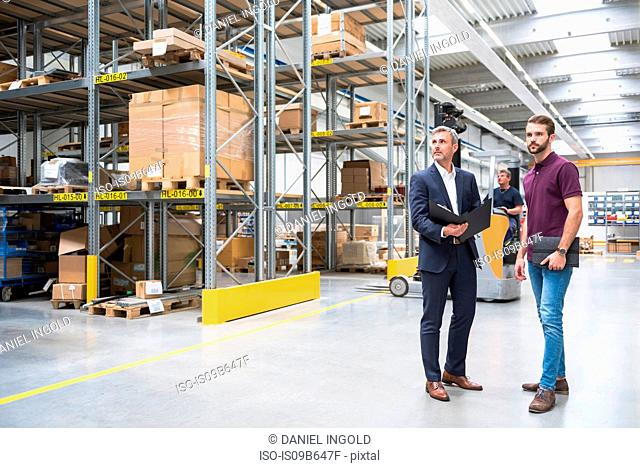 Warehouse worker and manager looking from aisle in distribution warehouse