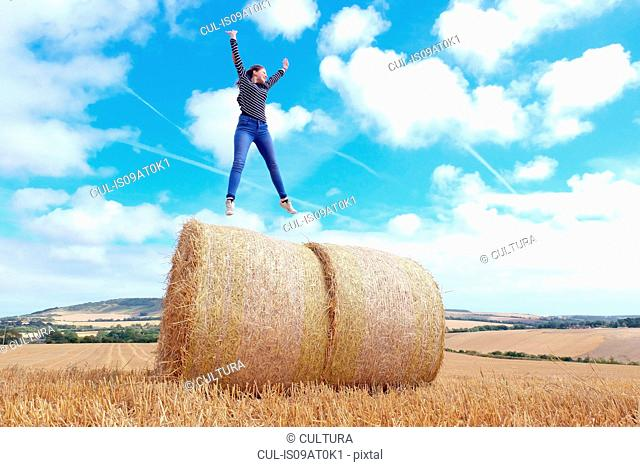 Young woman jumping on top of haystacks in harvested field
