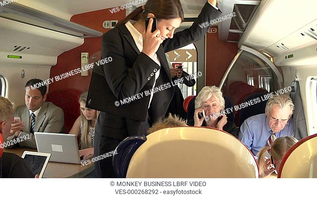 Crowded train carriage with passengers working on laptops and using mobile phones.Shot on Sony FS700 in PAL format at a frame rate of 25fps