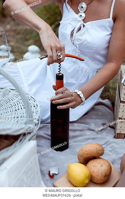 Woman opening bottle of wine at a picnic