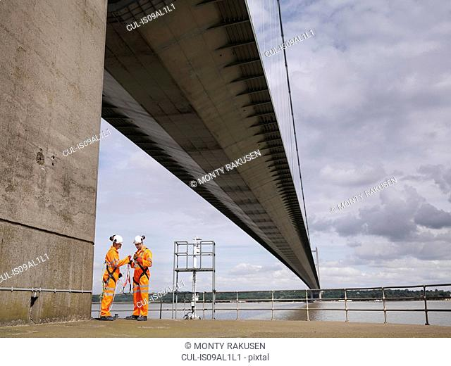 Bridge workers meeting under suspension bridge. The Humber Bridge, UK was built in 1981 and at the time was the world's largest single-span suspension bridge