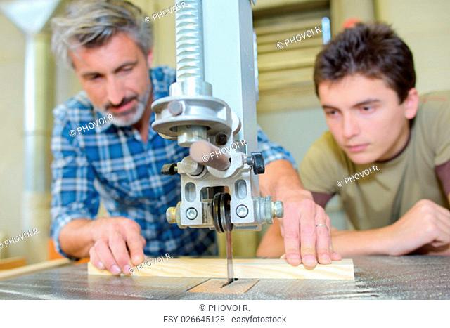 Carpenter teaching apprentice to use a bench saw