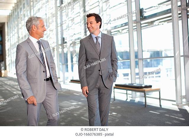 Two businessmen talking in modern lobby