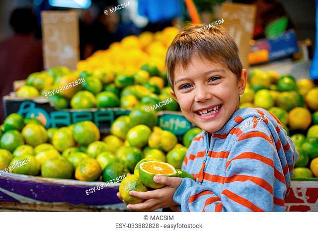 Portrait of cute boy with orange on the market