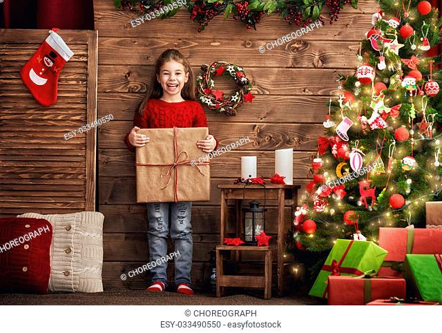 Merry Christmas and Happy Holiday! Cute little child girl with Christmas present. Kid holds a gift box