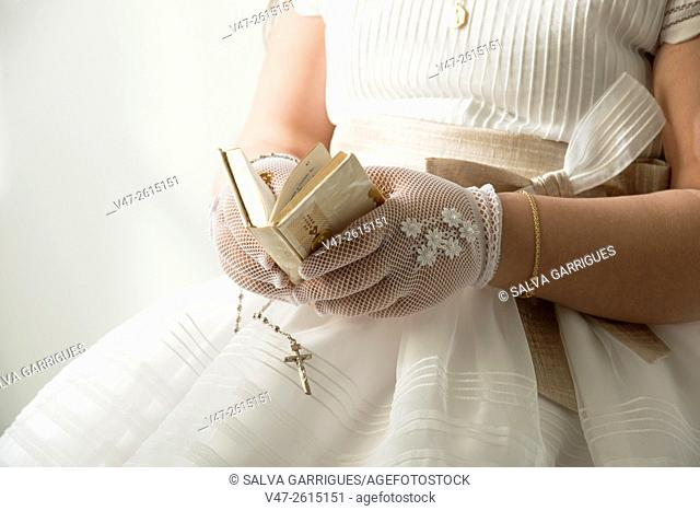 Girl reading the bible on the day of his first communion