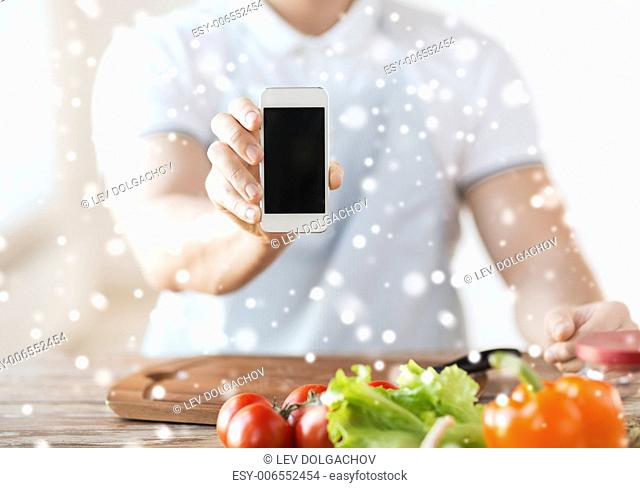 cooking, people, technology and home concept - close up of man with vegetables on table showing blank smartphone screen in kitchen