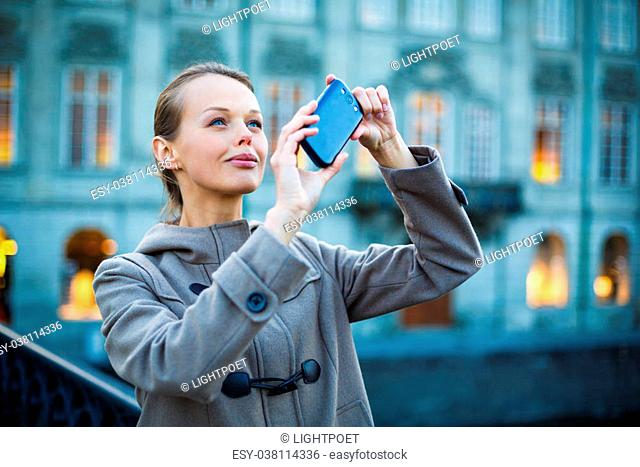 Elegant, young woman taking a photo with her cell phone camera while travelling (shallow DOF; color toned image)