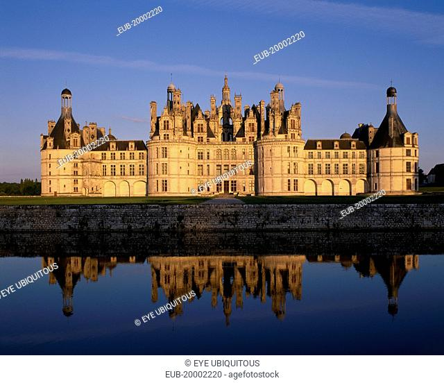 Chateau Chambord in golden light, reflected in moat in foreground