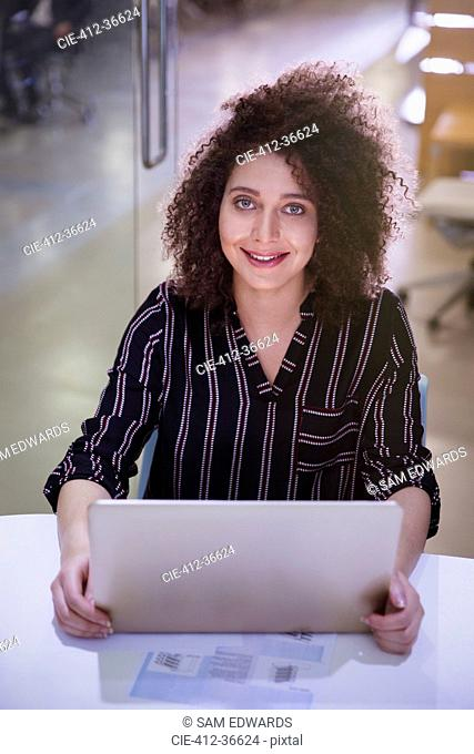 Portrait smiling, confident businesswoman working at laptop