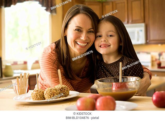 Caucasian mother and daughter making caramel apples