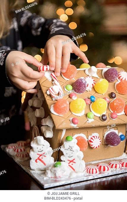 Hands of Caucasian girl decorating gingerbread house with candy
