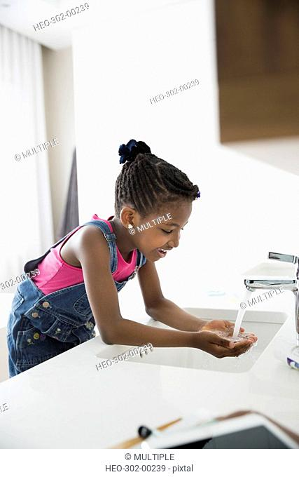 Girl washing face at sink in bathroom