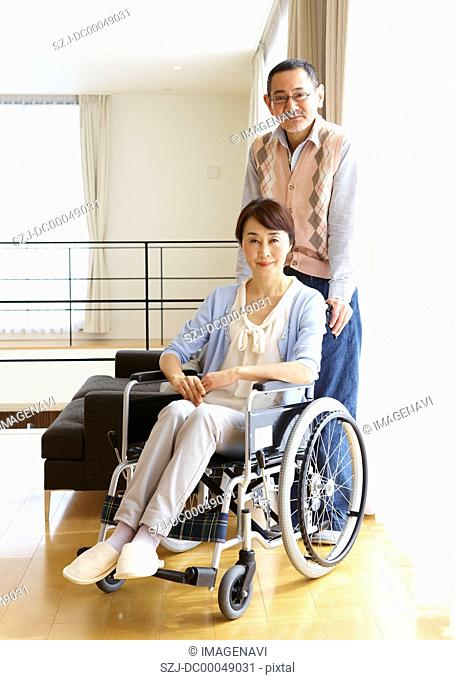 Senior man standing by his wife in a wheelchair
