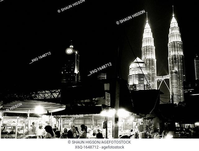 Night image of the Petronas Towers looming over the Malay area of Kampung Baru in Kuala Lumpur in Malaysia in Southeast Asia Far East
