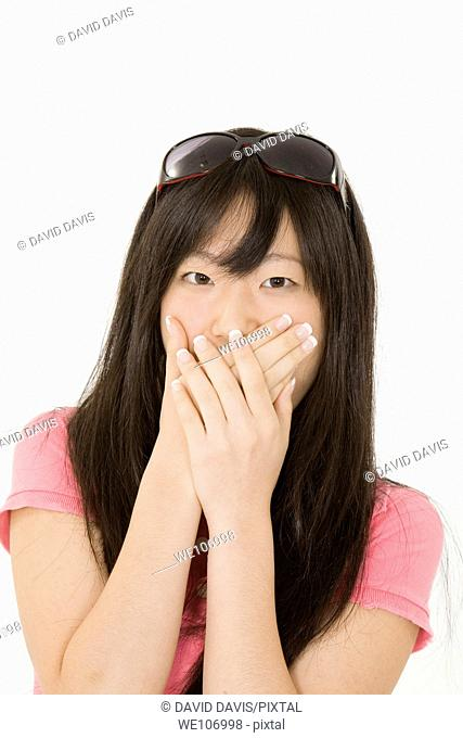 Portrait of a beautiful Asian teenager posing on a white background with hands over mouth