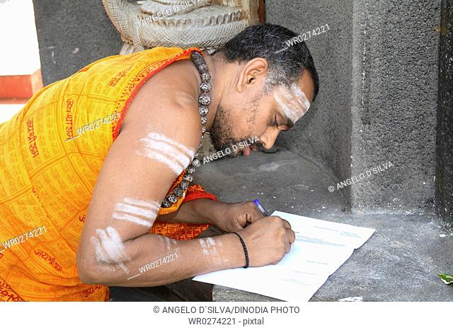 Religious preacher wearing rudraksha mala applying holy ash or bhasma with three bands on body standing outside Adi Shankaracharya temple ; Kaldi ; Kerala ;...