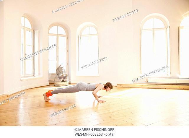 Woman in sunny yoga studio holding Chaturanga Dandasana pose