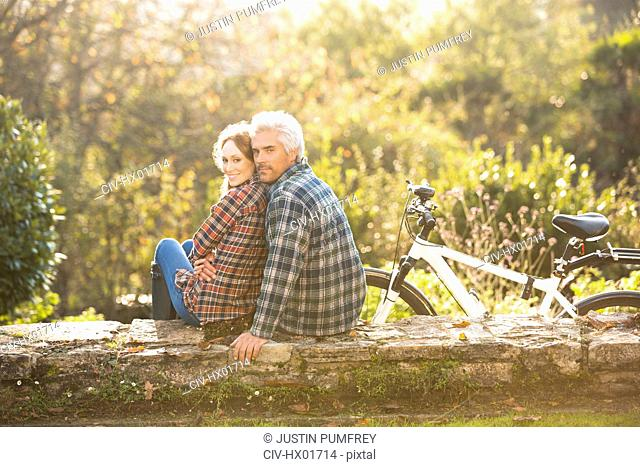 Portrait affectionate couple with bicycle resting on stone wall in autumn park