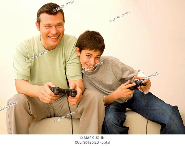 Boy and father playing with video game controllers on sofa