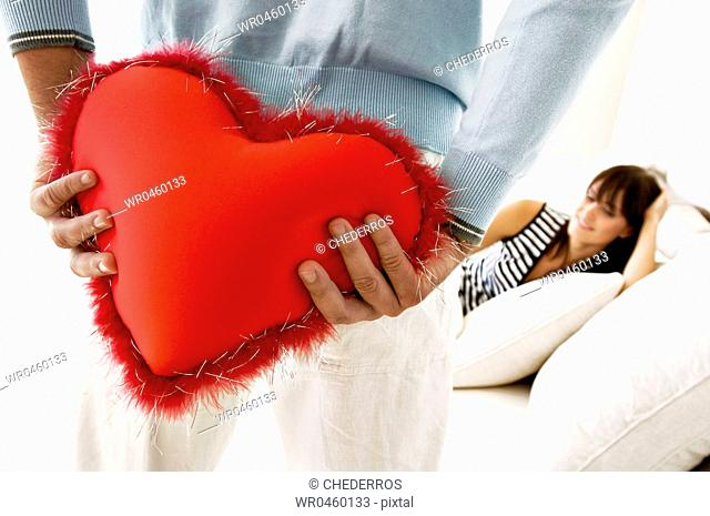 Mid section view of a man hiding a heart shaped cushion from a young woman