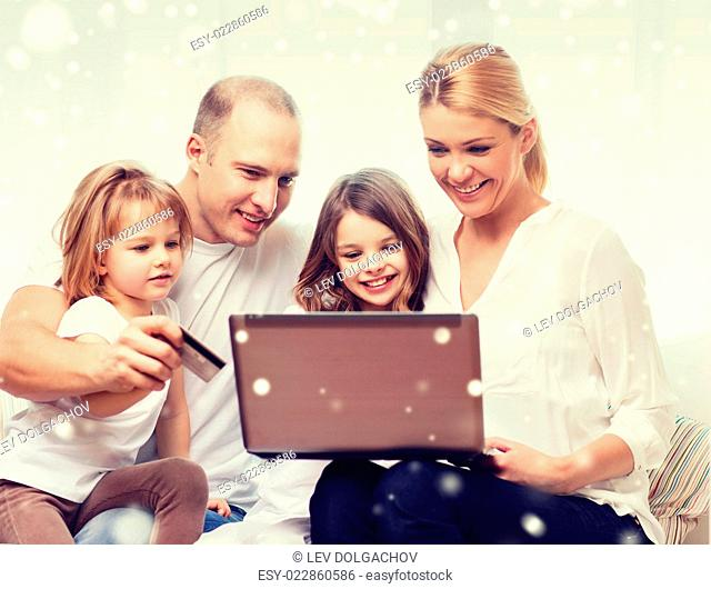 family, shopping, technology and people concept - happy family with laptop computer and credit card over snowflakes background