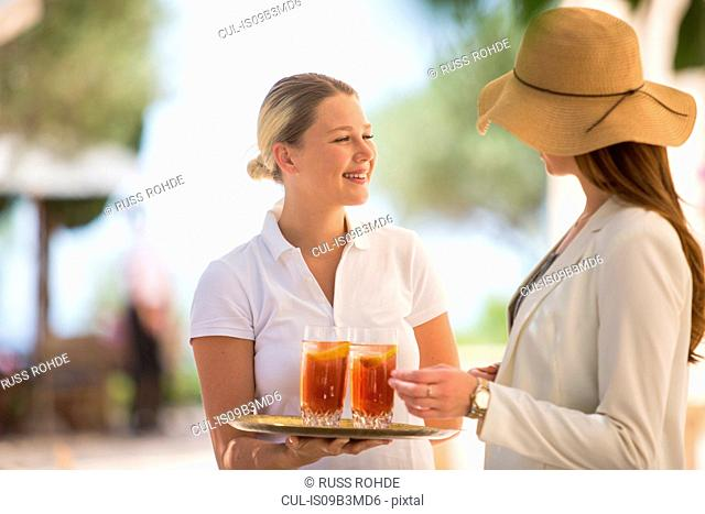 Boutique hotel waitress welcoming young woman with drinks, Majorca, Spain