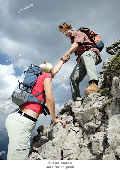Couple hiking up mountain, Kleinwalsertal, Allgau, Germany