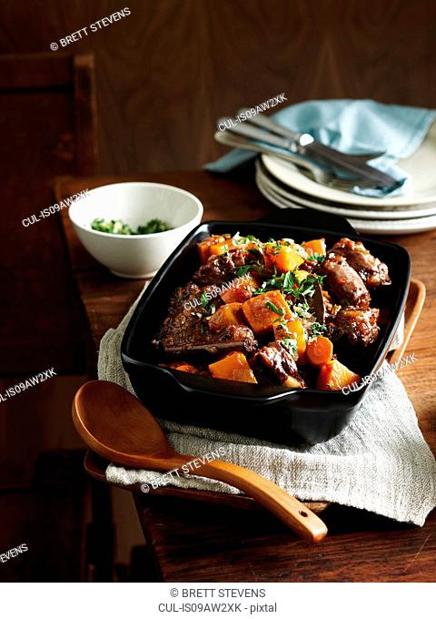 Middle eastern oxtail stew in serving dish with wooden serving spoon
