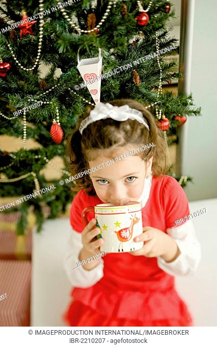 Girl sitting in front of a Christmas tree drinking from a cup