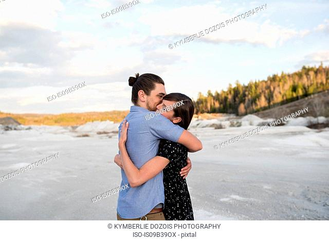 Couple hugging on snow-covered landscape, Ottawa, Ontario