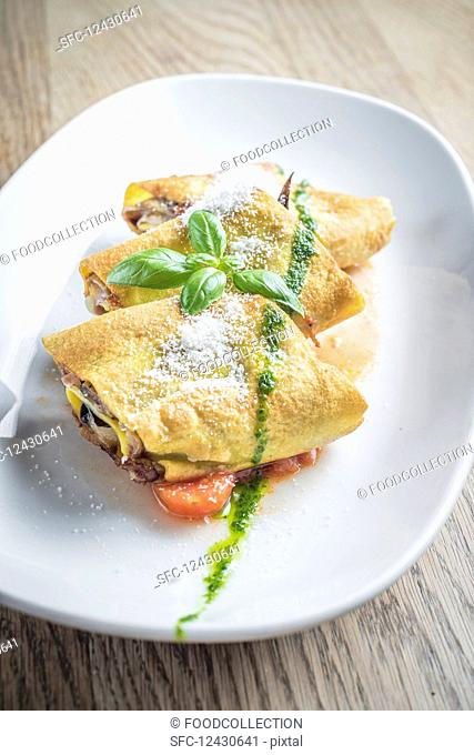 Egg crepes roll with vegetables and mushrooms in a tomato sauce with pesto dressing and a sprinkle of parmesan chees