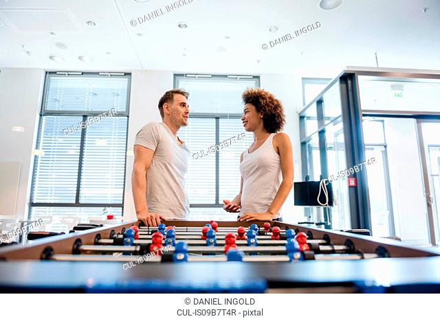 Couple leaning against table football table chatting