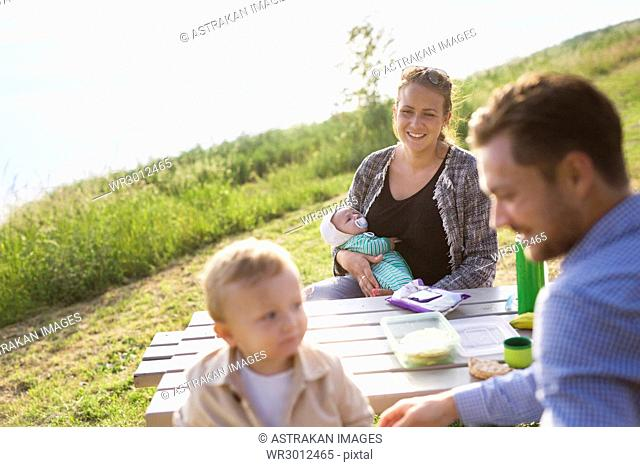Parents with sons (18-23, 0-1 months) sitting by picnic table